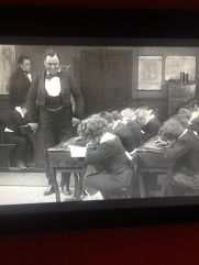 headmaster intrudes on Mr Mell's classroom; young David in first seat